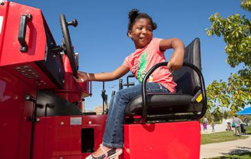 Young girl sitting on a big truck